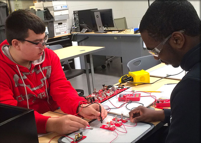 Two students performing electronic testing